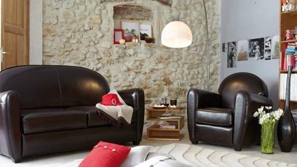 sala con sofás de cuero en tono marrón oscuro con revestimiento de